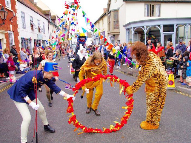 Watchet Carnival Parade with girl dressed as a lioness ducking through a hoop