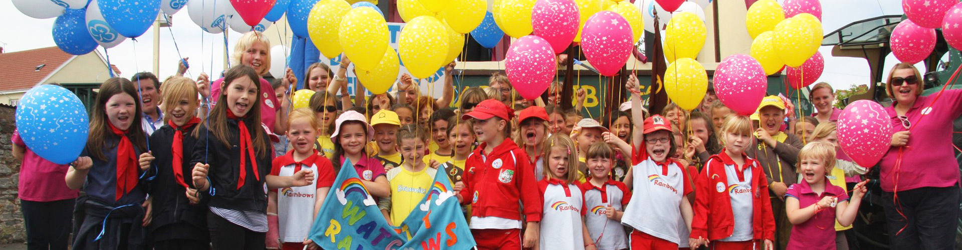 The Watchet Rainbows all holding balloons and cheering